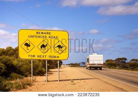 The famous sign on the Nullarbor Plain in Western Australia - look out for emus, camels and kangaroos. A caravan has just passed by the sign.