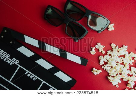 Cinema minimal concept. Watching film in the cinema. clapper board, 3d glasses, popcorn on red background.