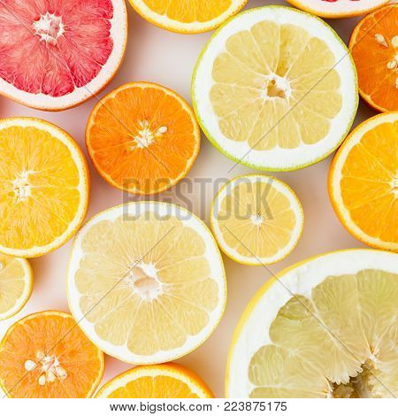 Citrus fruits pattern made of lemon, orange, grapefruit, sweetie and pomelo isolated on white background. Flat lay, top view. Fruit background