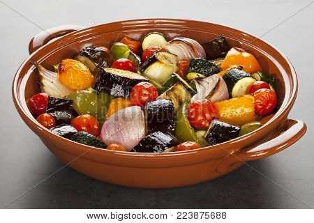 Ratatouille Roasted Mediterranean Vegetables - An earthenware dish filled with oven baked Mediterranean vegetables, or ratatouille.