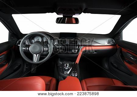 Modern luxury car Interior - steering wheel, shift lever and dashboard. Car interior luxury.Steering wheel, dashboard, speedometer, display. Red and black perforated leather cockpit isolated with clipping path