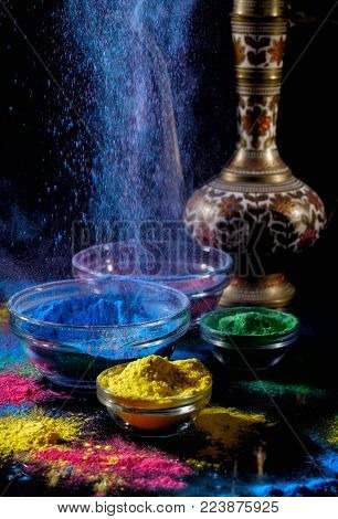 Indian Holi festival colours. Several bowls with Holi paint powder. Explosion of blue color on black background. Indian lipped jug.