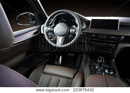 Modern luxury car Interior - steering wheel, shift lever and dashboard. Car interior luxury inside. Steering wheel, dashboard, speedometer, display. Brown leather cockpit