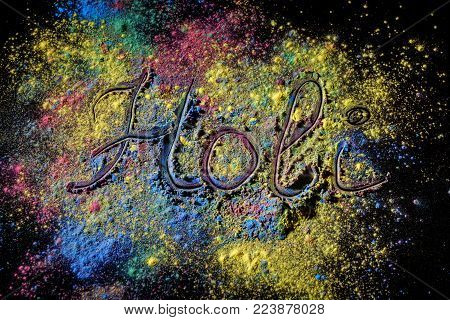 Holi paint festival background with lettering Holi . Color powder explosion on black surface.