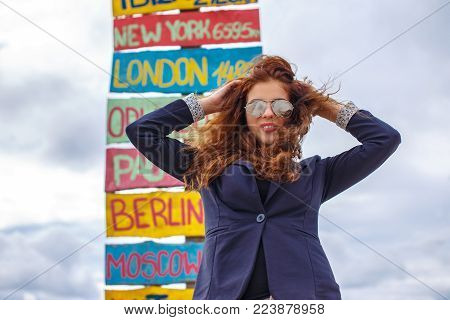 Beautiful redhead woman in sunglasses posing over direction signpost.