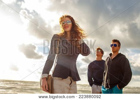 One redhead girl in sunglasses and two guys posing on a beach over grey sky.