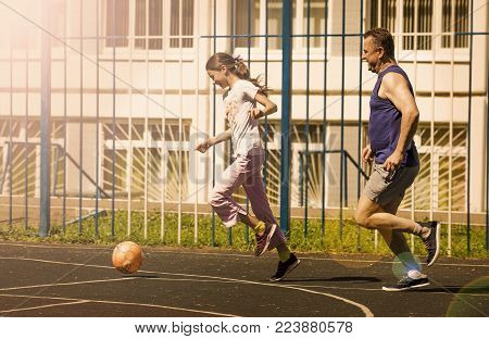 Father and dother playing soccer in a schoolyard.