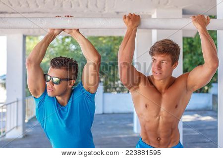 Two muscular guys posing with hands up. One of them in blue shirt and sunglasses.