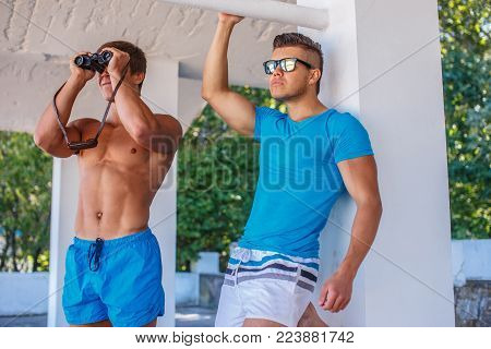 Two young muscular sea rescuers looking at people in binocular.