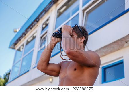 Smiling muscular guy in blue swimming shorts and sunglasses posing over rescue building.
