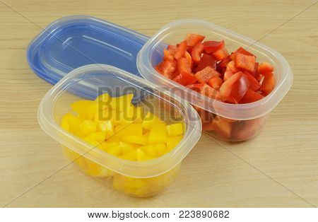 Chopped red and yellow bell peppers in plastic storage containers to organize of preparation or for planning in advance for quicker work week cooking time