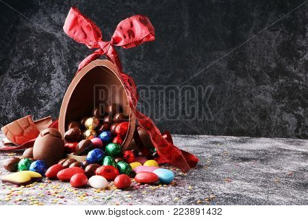 Chocolate Easter eggs with color ribbon bows on vintage background