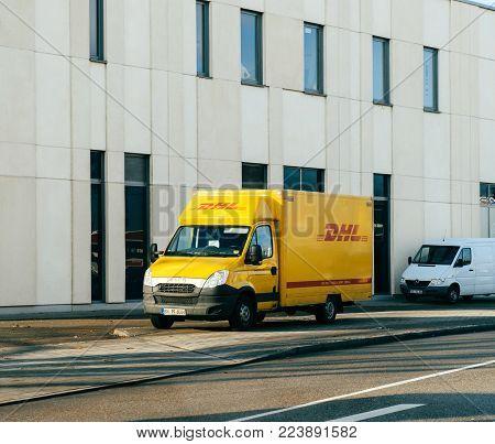 FRANKFURT, GERMANY - JAN 16, 2017: DHL Deutsche Post German postal yellow parcel distribution wvan parked on a German street near office industrial building mall store