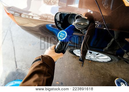 Point of view of man at the hand holding Super 95 E10 pumping gasoline fuel in car at gas station.