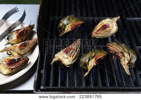 Grilled Artichokes: Artichoke halves on a gas grill. A plate of done vegetables is on the side tray.