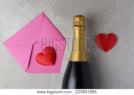 Valentines Day: Pink envelope and red heart next to a bottle of champagne.