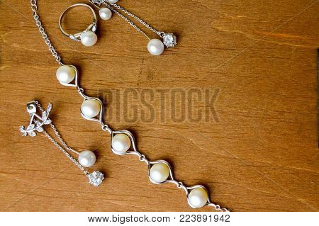 Beautiful rings, necklaces, earrings, jewelry with precious stones, pearls on a wooden brown background.