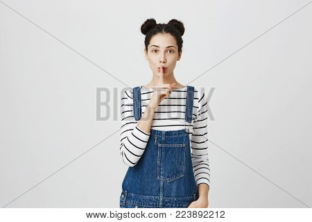 Pretty cute female with dark hair wears denim overalls looks at camera keeps finger on lips, asks not to make noise and to keep her secret, poses in studio. Horizontal shot of attractive woman makes hush gesture