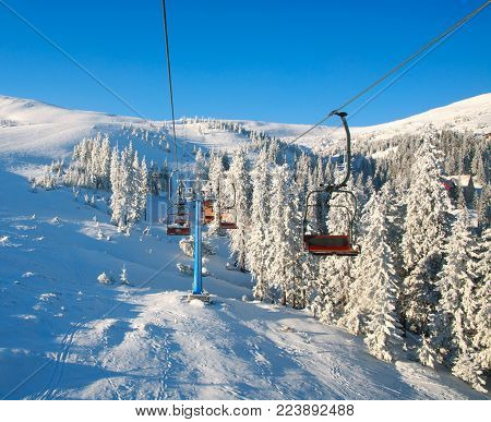 Ski lifts in the snowy mountains and spruce forest on a background of blue sky