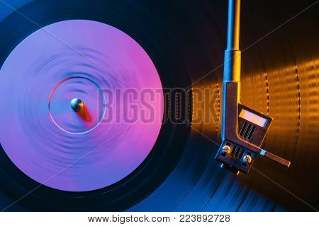 Movie of retro-styled record player spinning vinyl black record. Cinemagraph. Side view. Beautiful neon night colors.