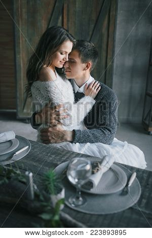 A young woman sits on man's lap in the kitchen. Couple in love. Artwork.