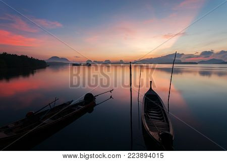 Longtail boat with coastal fishing village,Beautiful scenery view in morning sunrise over sea and mountain at phang - nga thailand.