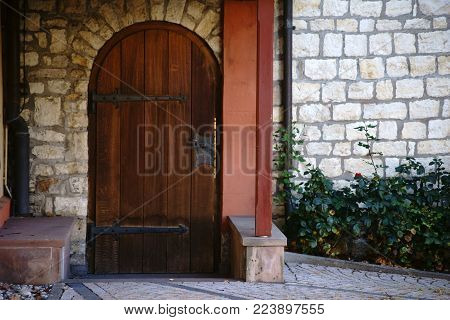 A heavy wooden church door with wrought-iron hinges.