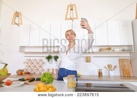 Marvelous girl housewife with smartphone communicates by video call with husband and greets with hand, with smile on face shows what she preparing for dinner and directs camera to cucumbers and tomatoes with lettuce, pasta and fruit in bowl, standing agai