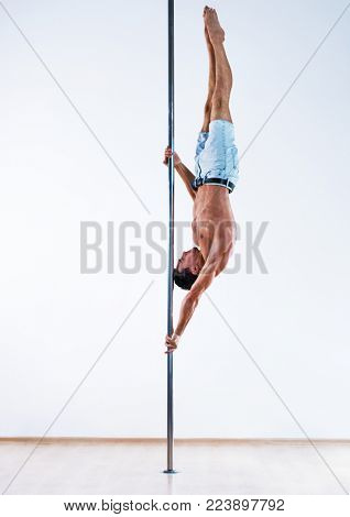 Young pole dancing man on white wall background