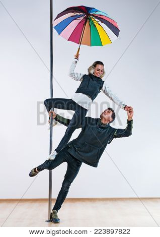 Young man and woman pole dancers in casual autumn clothing with umbrella