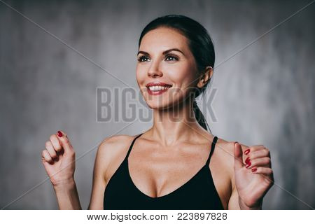 Young happy smiling brunette woman portrait on gray wall background
