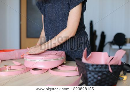 Seamstress took part in competition and won pink leather backpack and purse. Happy young woman standing near table with tools and products in workshop at home, viewing present and showing on camera. Concept of giveaway, useful gift or stylish accessories.
