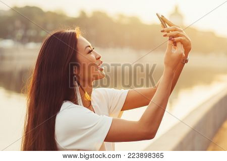 Young asian woman doing selfie on city river background at sunny morning