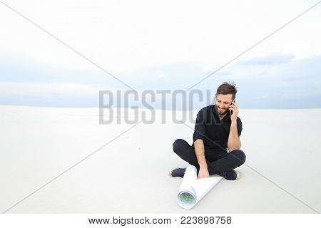 constructor talk on smartphone, bearded fellow waiting for friend to work on project of waste processing plant in countryside. Young fair-haired man wearing black shirt trousers sitting on sand holding whatman paper. Concept of fashionable clothes, stylis
