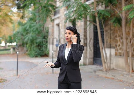 Young color female person typing message by smartphone  to truelove and asking about date. Mix blood woman wears classic suit. Concept of communication, modern technologies and talking in good Internet.
