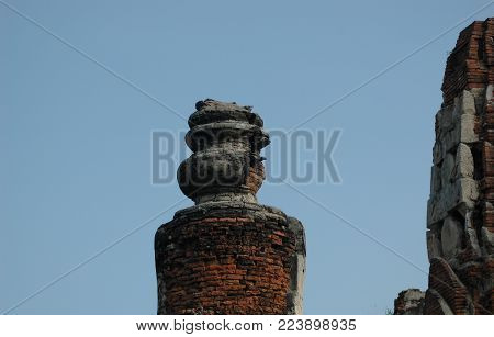 Closeup of ruins in a temple in Thailand. Much of the grey stone has been removed, revealing red bricks. The remains of an urn beside a large tower are visible against a clear blue sky.