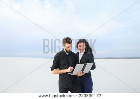 Girlfriend and boyfriend using laptop to talk with parents at seaside, couple go to business trip. Fellow and girl in strict suits standing among sands demonstrating nature with web-camera. Concept of innovative technologies, gadgets or video call for com