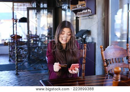 Teacher check tests in cafe using smartphone, young Asian woman sitting near table with phone in pink case in hands waiting for order. Interior decorated with antique wooden furniture big windows. Concept of cozy luncheonette, quite place for work and per