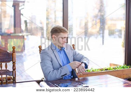 Businessman enjoying smart watch at cafe with tablet, roll project and black document case on table. Young man waiting for biz meeting and job interview. Concept of using modern devices for work.