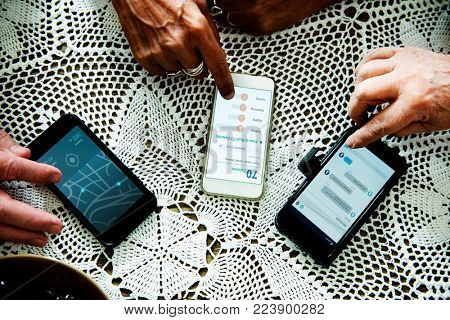Closeup of old people hands using mobile phone