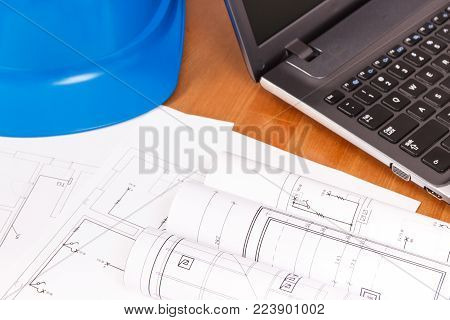 Diagrams or electrical construction drawings with laptop and protective blue helmet for engineer jobs lying on desk, technology concept