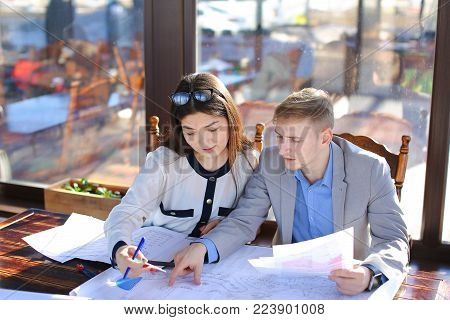 Young female student talking with architecture professor about course project. Pretty girl dressed in blouse speaking with man in grey suit. Concept of educational consulting at catering establishment. poster