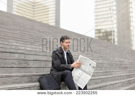 effect. Tutor dressed in gray coat sitting on rung and read morning newspaper. Articles pleased man and caused smile. Male turn edition for read any good news. Concept of positive emotions from good news.