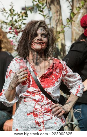 ATLANTA, GA - OCTOBER 2017:  A woman dressed like a bloody zombie enjoys a beer while waiting for the start of the Little Five Points Halloween Parade in Atlanta, GA on October 21, 2017.