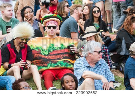 ATLANTA, GA - OCTOBER 2017:  A man wearing a hamburger costume sits with a crowd of spectators as they await the start of the Little Five Points Halloween parade in Atlanta, GA on October 21, 2017.