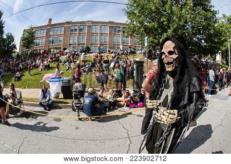 ATLANTA, GA - OCTOBER 2017:   A person dressed as the grim reaper walks by a crowd gathering to watch the Little Five Points Halloween Parade in Atlanta, GA on October 21, 2017.