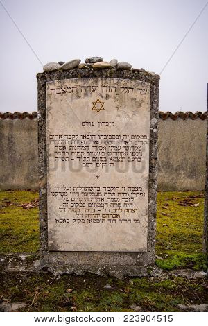 Burghausen,Germany-Jan 26,2018: On the Holocaust meorial day a headstone in hebrew  in a cemetery in an outpost of the Dachau Concentration camp remember the jewish prisoners that died at the site.