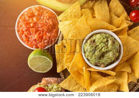 Tradition mexican guacamole and salsa dip, nachos tortilla chips, close-up.