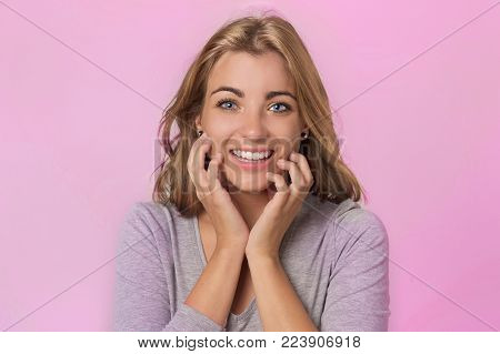 portrait of young pretty and attractive blond Caucasian girl with beautiful blue eyes on her 20s excited and happy smiling cheerful in sweet face expression isolated on pink background