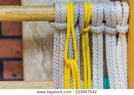 white and yellow ropes tied in knots and hang in a row